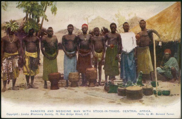 Central African medicine man with apparatus and attendant musicians and dancers