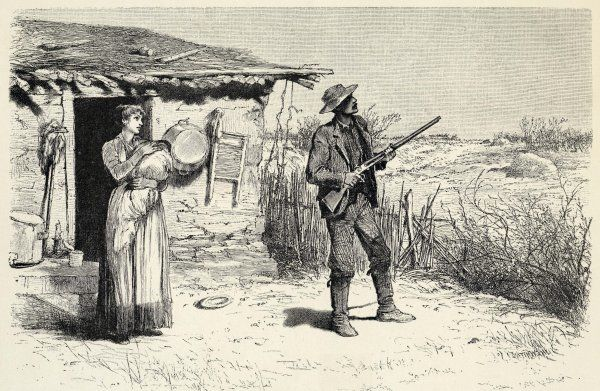 A settler stands ready with a gun outside his shack, with tin bath and washboard hung on the outside wall, while his wife comforts the baby