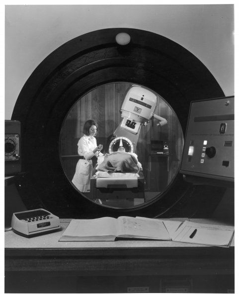 A patient seen through a circular zinc bromide safety window, containing a theratron 80 unit used for radiation treatment, Churchill Hospital, Oxford, England