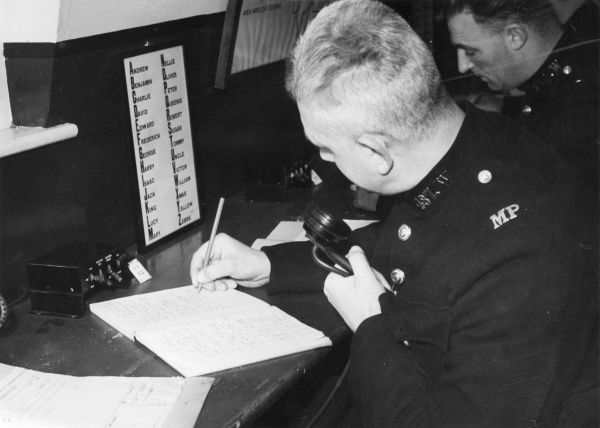 Radio Operator - Metropolitan Police. A list of a name form of the phonetic alphabet is propped up on his desk Date: circa 1940s