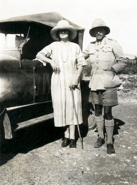 An RAF officer and his wife standing at the side of a motor car, somewhere in the Middle East