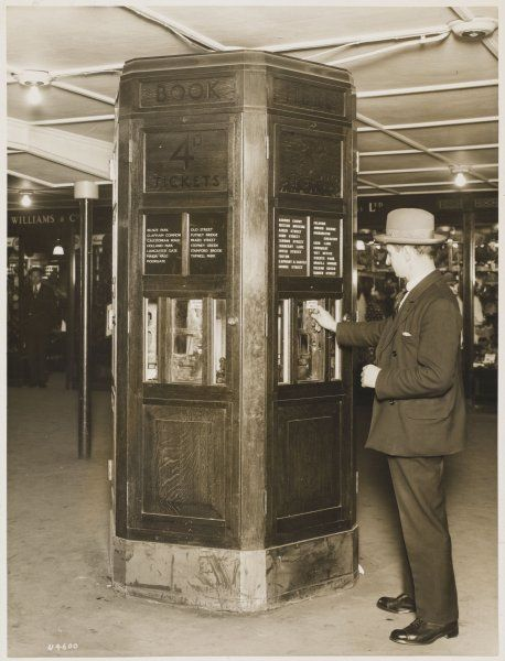 A man buying a ticket from a ticket machine in an unknown London underground station