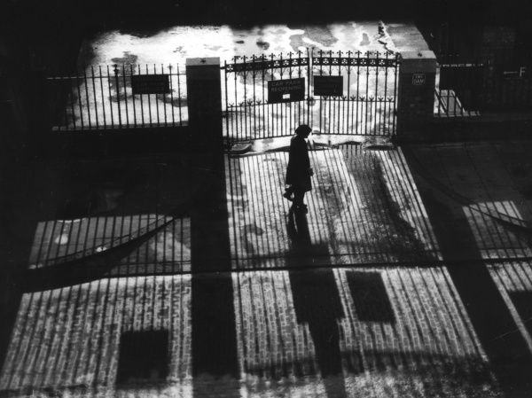 Iron gates and railings cast sinister shadows across a young woman walking alone at night... Date: 1950s