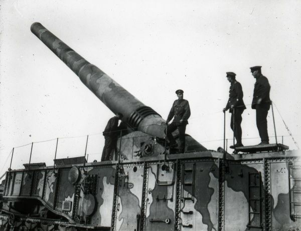 A railway mounted gun emplacement and soldiers during the First World War. The gun and mounting have been camouflaged with two shades of paint