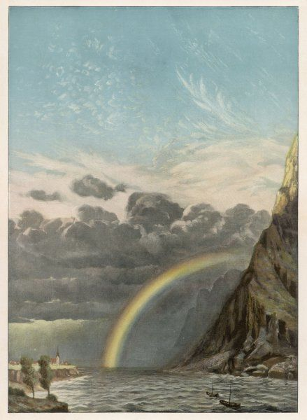 A rainbow appears above the sea betwixt a mountain range and a coastal town. The sky remains dark and forboding