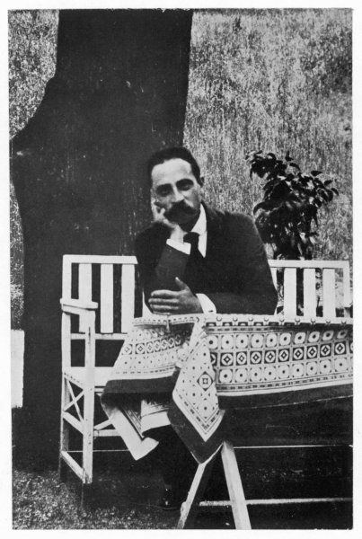 RAINER MARIA RILKE German poet sitting at a table in a garden