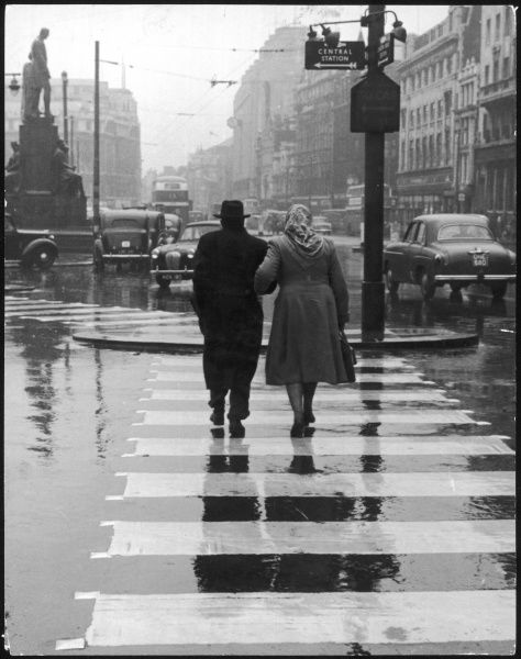 A typical English street on a rainy shopping day: an elderly couple use the zebra crossing