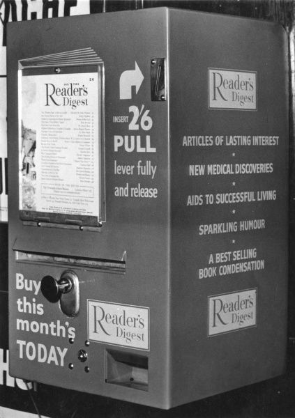 A vending machine dispensing copies of the Reader's Digest at Exeter St David's station in Devon. At this date, before decimalisation of the currency, the price is two shillings and sixpence (half a crown)