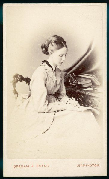A vignette photograph showing a young woman wearing a polonaise with over-skirt divided at the front. Hair: centre parting with large coils of false hair