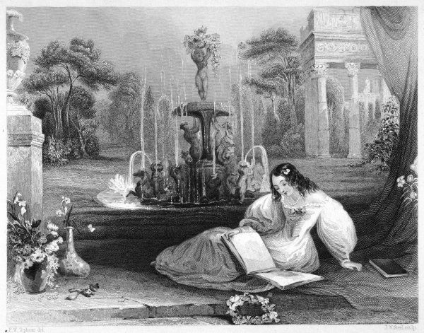 A girl in a white dress with flowers in her hair reads in the garden beside an elaborate fountain