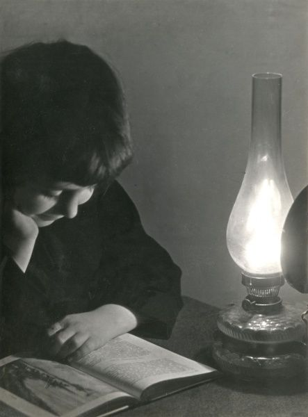 A young boy reads a book by lamplight Date: 1940s