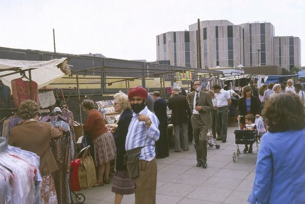 A Seikh man among the shoppers at Reading Market, Berkshire, England. Date: 1980