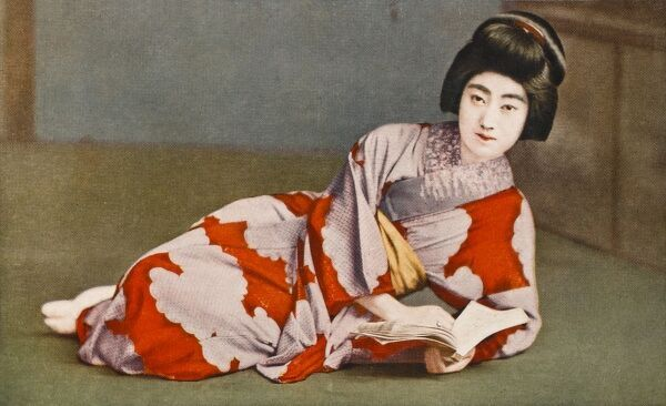 A reclining Japanese geisha beauty reads from a text