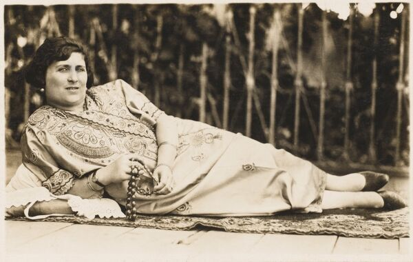A fine photograph postcard depiction of a reclining Turkish woman, holding a string of prayer beads (Tesbih)