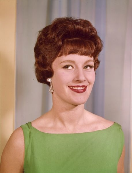 A head and shoulders portrait of a woman with deep auburn hair in a style typical of the late 1950s or early 1960s. She also wears a green dress, earrings and bright lipstick