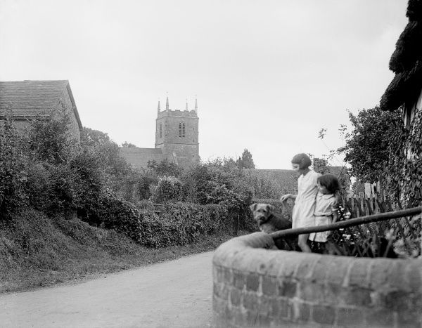 Two little girls and their pet dog in the village of Redmarley D'Abitot, Gloucestershire, England. Date: early 1930s