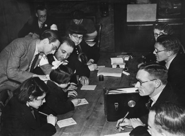 An official interpreter at the distributing centre helps Belgian refugees fill our food ration cards during World War II