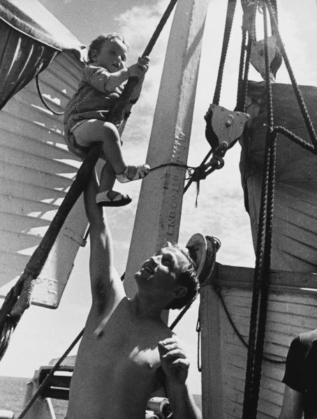 Refugees on a ship, with child playing in the rigging during World War II