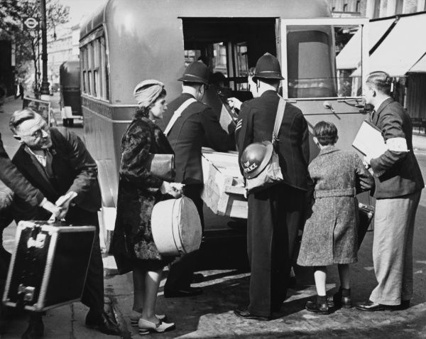 London police carrying gas masks and steel helmets help the refugees to load their luggage on the bus in London during World War II