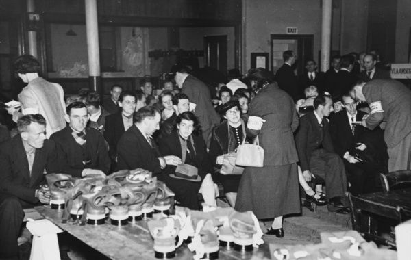 Officials of the Fulham Borough Council in London take down particulars from refugees in the waiting room of the distributing centre. Note pile of gasmasks in the foreground
