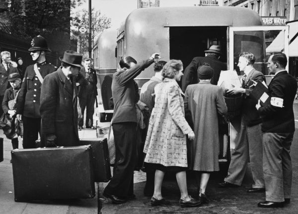 Refugees, including Jenny de Graaf, board the bus from the receiving centre to distributing centre in Fulham, London, during World War II
