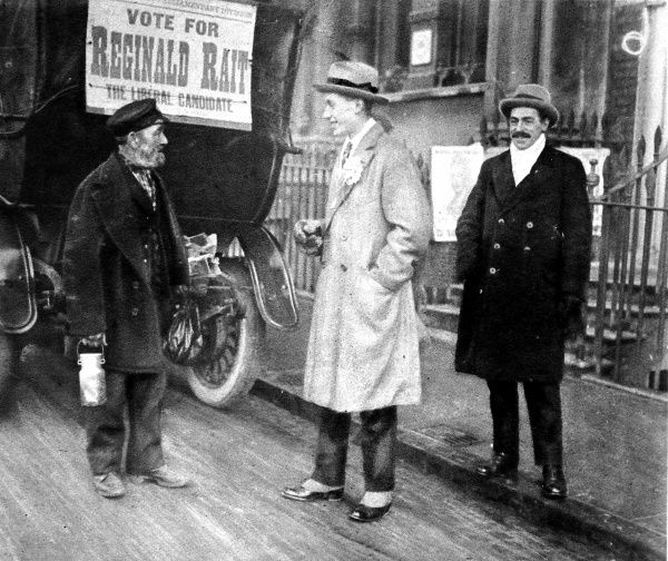 Photograph showing the youngest candidate standing in 1923, Reginald I. Rait (Liberal) (centre of image), canvassing a voter in the Isle of Thanet