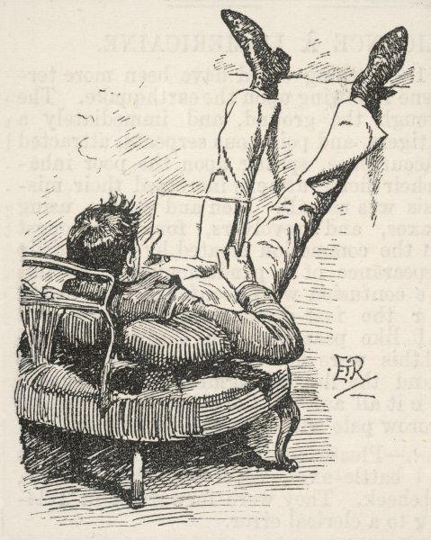 A young man, with his upper body propped up on cushions on a day bed, rests his feet up on a ledge in order to create the perfect reading posture