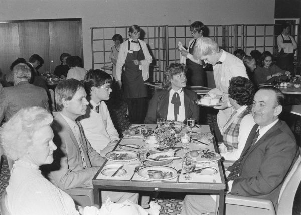 A group of friends, colleagues or relatives eat out at a rather tawdry restaurant with interesting lino. Note the dour looking waiters and waitress!