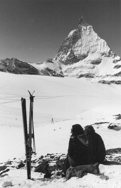 A couple of skiers taking a rest, Switzerland.  1960s