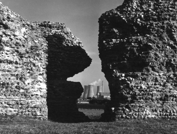 Ancient and modern, a view of the remains of Richborough Castle, built by the Romans on the coast of Kent, England. Note the glimpse of a 'modern' power station behind. Date: 1st century