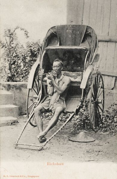 A Rickshaw Driver from Singapore and his vehicle. He has stopped off for a puff on his pipe
