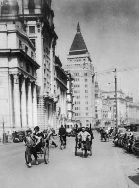 A busy street scene on the Nanking Road, Shanghai, China, showing rickshaws outside the Cathay Hotel