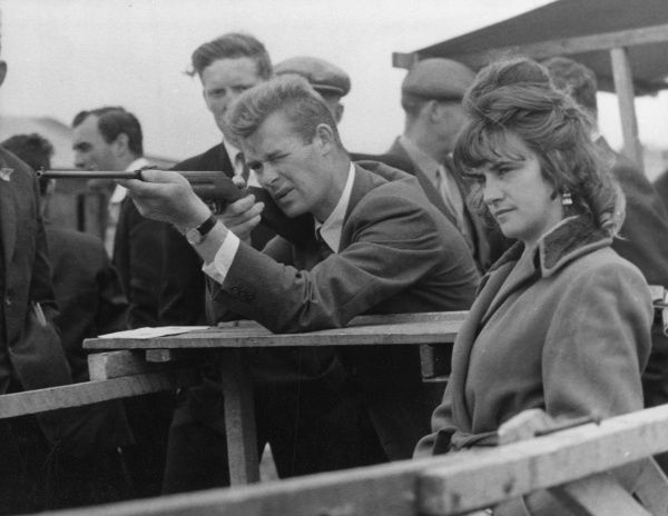 A young man tries to impress his girl, by aiming for the Bull's Eye on a fairground Rifle Range at Dingle racecourse, County Kerry, Ireland. Date: 1962