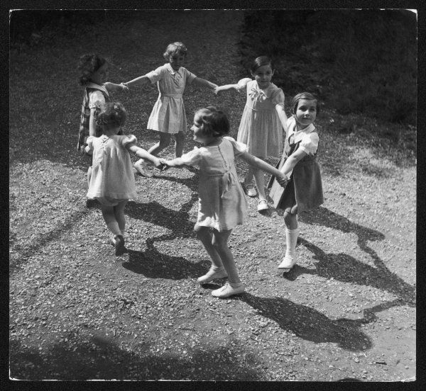 A group of girls play Ring O' Roses holding hands