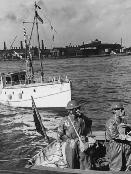 River Emergency Service, World War II. A patrol boat of the River Emergency Service returning from duty flies the gas signal GQH and a member of the crew signals for assistance be semaphore