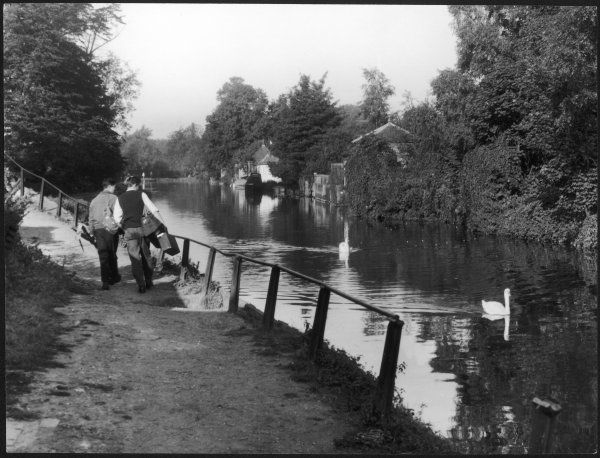 Two young men, on their way home from a days' fishing, pause to admire the swans on the River Lea at Ware, Hertfordshire
