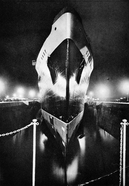 Photograph of the bow of R.M.S. 'Queen Mary', taken at night, whilst she was in dry dock to have her hull repainted and her four propellors changed. Each propellor on the luxury Cunard White Star Liner weighed approximately 35 tons