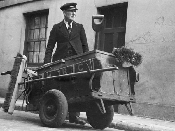 A road sweeper with his cart, containing various brushes and a spade. He probably works for the St Marylebone Borough Council in London