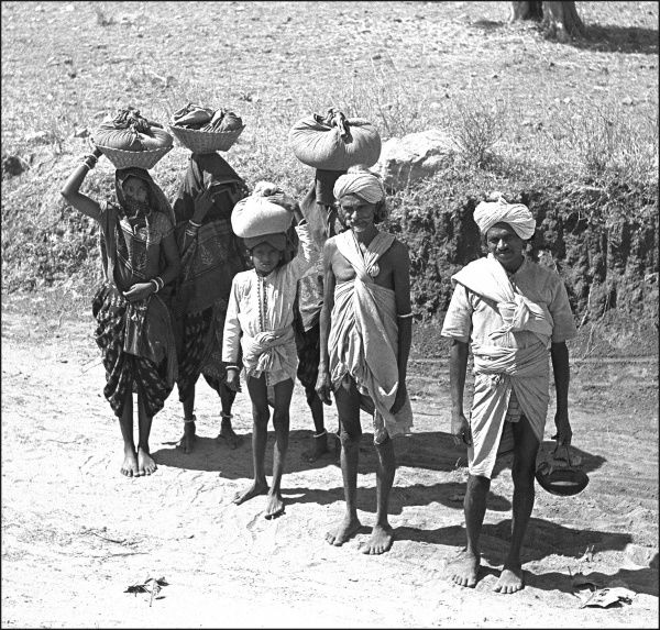 Men women and children, some carrying wrapped goods on their heads, pose for a picture on the roadside in Madhya Pradesh Province, India. Photograph by Ralph Ponsonby Watts Date: circa 1940s