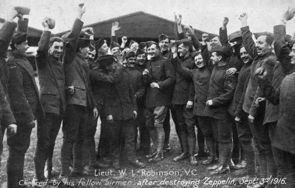 Pilot W I Robinson, who downed a Zeppelin, is cheered by his comrades. Date: 3 September 1916