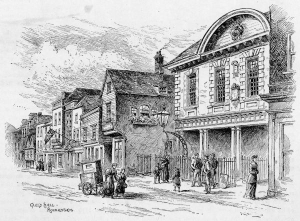 An organ grinder drags her organ along the High Street at Rochester, Kent, passing the Guildhall : Baggins' wonderful bookshop is further down the street to the left
