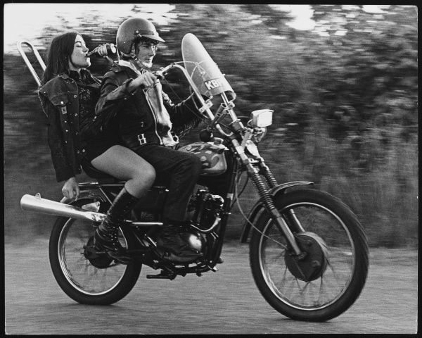 Rebellious teenagers on a motorbike in Charlwood, Surrey. They are wearing their leathers, and the girl is swigging a bottle of shandy!