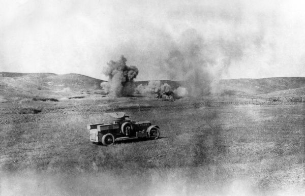 A Rolls Royce armoured car belonging to the Dunsterforce, with explosions from shelling in the background, during the First World War