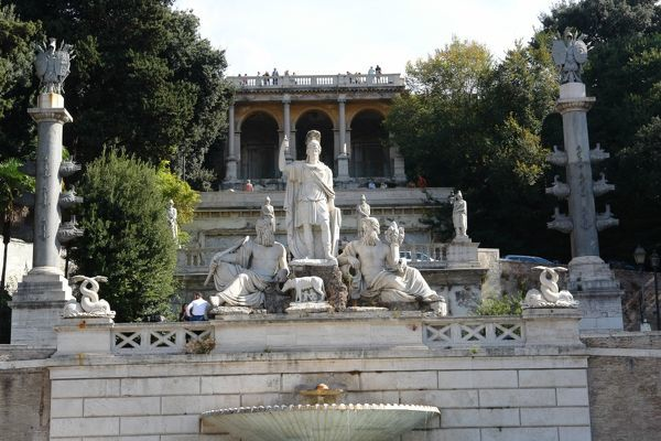 View of the Romulus and Remus Fountain (Fontana della Dea Roma) in the Piazza del Popolo in Rome, Italy. The fountain represents the goddess Dea Roma armed with lance and helmet. In front of her is a small sculpture of the she-wolf feeding Romulus