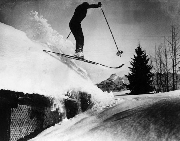 Some people stop at nothing and this ski jumper goes over a snow clad roof just to keep in practice! Date: 1930s