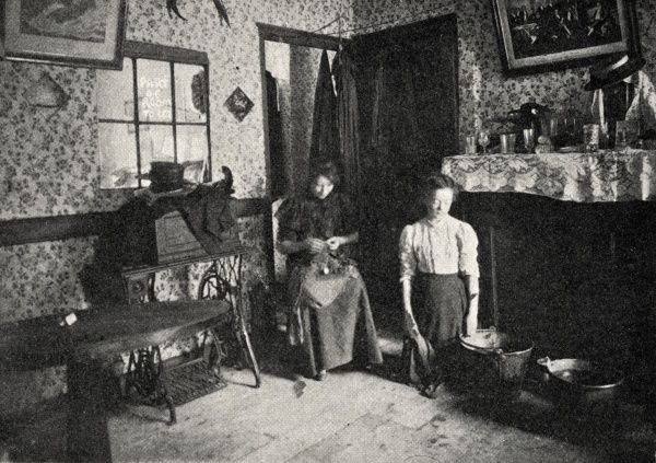 Interior of a house in the East End of London where the demand for cheap accommodation was such that even a part of a room might be sub-let as indicated by the notice on the window. The room's bare floor is being cleaned by a woman with two large buckets