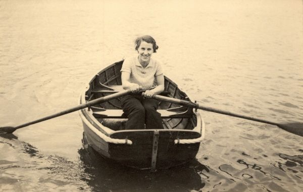 A woman sits and rows a boat single-handedly on the Norfolk Broads during the 1930s
