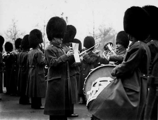 One of the Royal Guards holds up some sheet music for his colleagues in the brass band to read! Date: 1960s