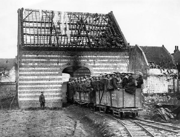 A Royal Engineers working party travelling in trucks on a light railway, passing through a ruined building at Arras, northern France, during the First World War. Date: March 1918