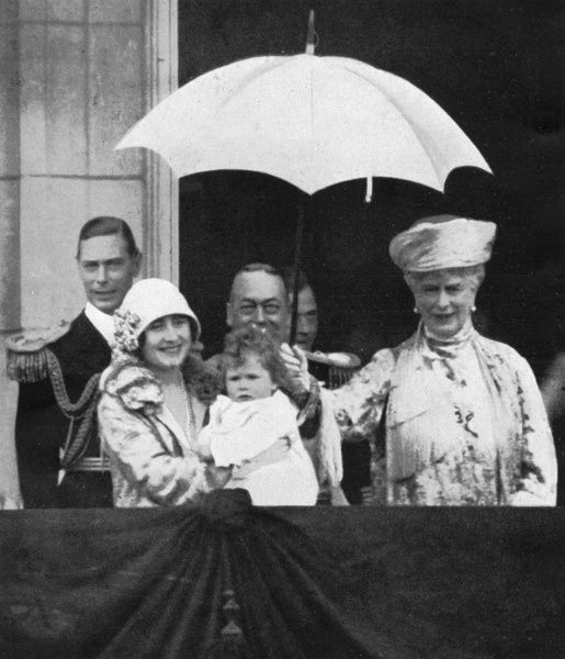 The King and Queen and Duke and Duchess of York, with little Princess Elizabeth, wave to crowds from the balcony of Buckingham Palace. Queen Mary holds an umbrella over the infant. Date: 1927